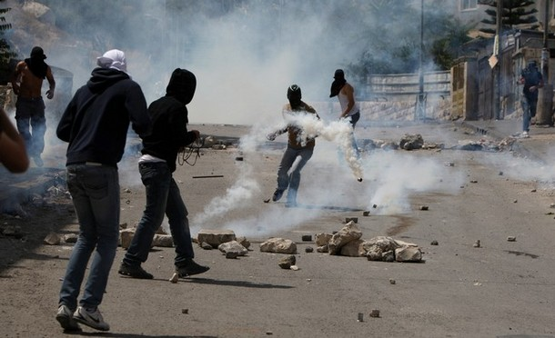 Masked Palestinian youths stand amidst t