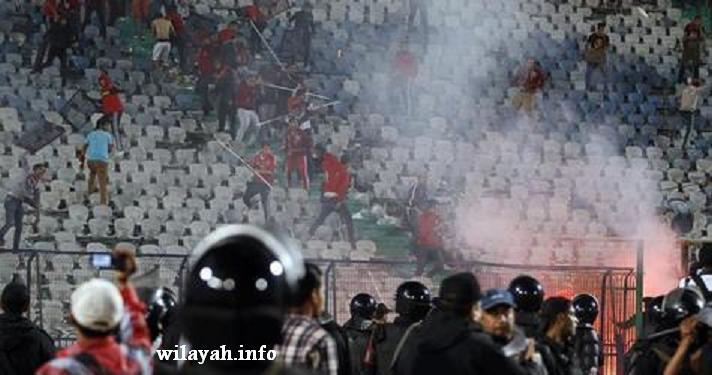 Fans of Egypt's Al-Ahly flee after riot police fired tear gas during clashes after their African Super Cup soccer match against Tunisia's CS Sfaxien at Cairo Stadium