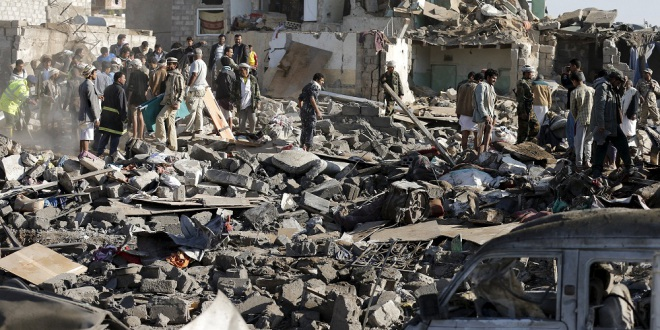 Civil defence workers and people search for survivors under the rubble of houses destroyed by an air strike near Sanaa Airport