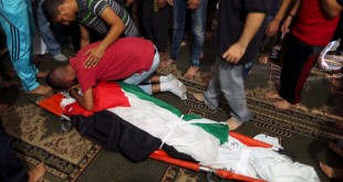 mourner reacts over the body of 21-year-old Palestinian Shadi Dowla, who was shot by Israeli troops during clashes in Gaza