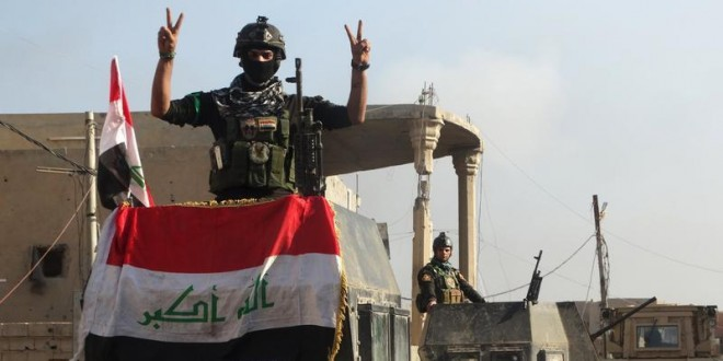 A member of the Iraqi security forces gestures at a government complex in the city of Ramadi