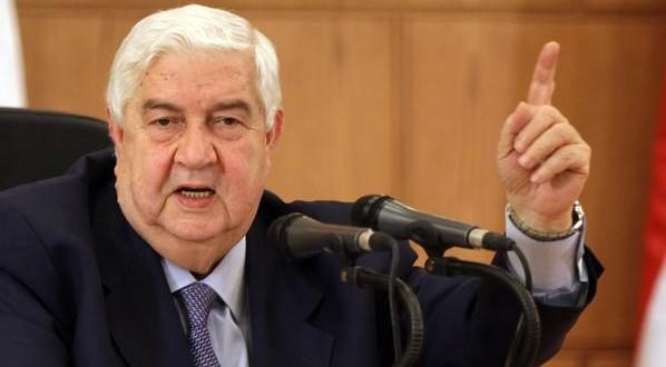 Seated under a portrait of Syrian Presid
